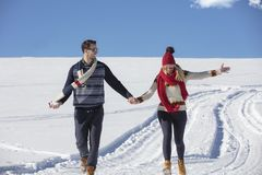 Happy couple playful together during winter holidays vacation outside in snow park Royalty Free Stock Photos