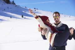 Happy couple playful together during winter holidays vacation outside in snow park Stock Photography