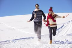 Happy couple playful together during winter holidays vacation outside in snow park Stock Photo