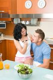 Happy couple playfully eating salad at kitchen Stock Images