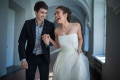 Happy couple playfully goes down a long corridor Royalty Free Stock Photos
