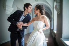 Happy couple playfully goes down a long corridor Royalty Free Stock Photography