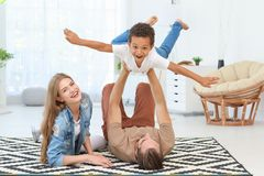 Happy couple playing with adopted African-American boy. On carpet at home Royalty Free Stock Photo