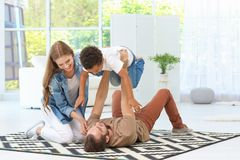 Happy couple playing with adopted African-American boy. On carpet at home Royalty Free Stock Image