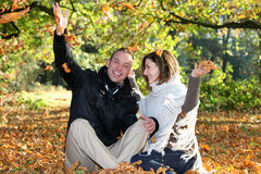 Happy couple playing with autumn leaves Royalty Free Stock Images