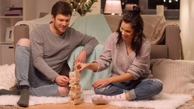 Happy couple playing block-stacking game at home stock video footage