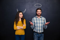 Happy couple playing devil and angel over blackboard background Royalty Free Stock Image