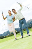Happy couple playing golf Stock Image