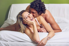 Happy couple playing and joking in bed Royalty Free Stock Images
