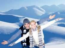 Happy couple playing outdoor at winter mountains. Happy couple having fun, raised arms flying hands, outdoors at winter snowy mountains, people at nature, blue Royalty Free Stock Photos