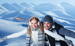 Happy couple playing outdoors. In winter, imitate the flight by hands, having fun together in the snowy mountains, with pleasure spending Christmas holidays Stock Photo