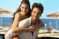 Happy couple playing piggyback at seaside beach Royalty Free Stock Photography