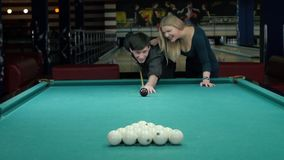 Happy couple playing pool. she supports her. Partner. The action takes place in the entertainment center stock footage