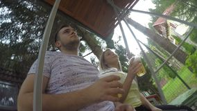 Happy couple playing in swing in the backyard toasting and drinking beer from recyclable glasses celebrating vacation -. Happy couple playing in swing in the stock video