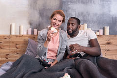 Happy couple playing video games in bedroom. Pretty weekend. Happy young international couple playing video games and eating cupcakes while lying in bed together Royalty Free Stock Images
