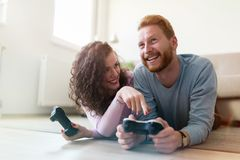 Happy couple playing video games at home Royalty Free Stock Images