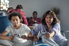 Happy couple playing video games at the modern startup office stock photos