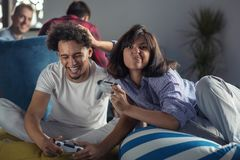 Happy couple playing video games at the modern startup office royalty free stock photo