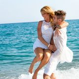 Happy couple playing in waves. Royalty Free Stock Photo