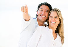 Happy couple pointing away Stock Photo