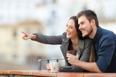 Happy couple pointing away in a balcony. With a town in the background royalty free stock image