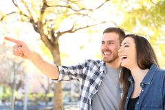 Happy couple pointing away laughing in a park royalty free stock photography