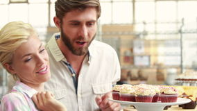 Happy couple pointing cupcakes at restaurant
