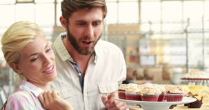 Happy couple pointing cupcakes at restaurant stock footage