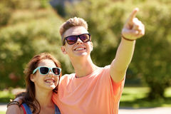 Happy couple pointing finger at summer park Stock Image
