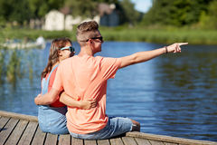 Happy couple pointing finger on summer river berth Royalty Free Stock Image