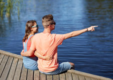 Happy couple pointing finger on summer river berth Royalty Free Stock Images