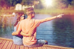 Happy couple pointing finger on summer river berth Royalty Free Stock Photo