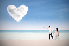 Happy couple pointing at heart Royalty Free Stock Photography