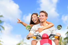 Happy couple pointing on scooter travel vacation. Young Asian women showing her boyfriend a location while driving a moped on a road trip during summer Stock Photos