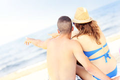 Happy couple pointing at something at the beach. A picture of a happy couple pointing at something at the beach Royalty Free Stock Images