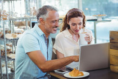 Happy couple pointing something on laptop Stock Photo