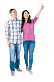 Happy couple pointing upwards Stock Photo