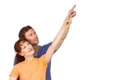 Happy couple pointing upwards together Stock Photo