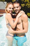 Happy couple in the pool embracing. And looking at the camera Royalty Free Stock Photography