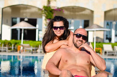 Happy  couple    on a pool. Happy couple  hugging on  the pool in luxury hotel Royalty Free Stock Images