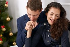 Happy couple portrait near christmas tree, drinking coffee and talking - love and holiday concept Stock Images