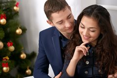 Happy couple portrait near christmas tree, drinking coffee and talking - love and holiday concept Royalty Free Stock Image
