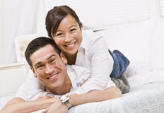 Happy Couple Posing on a Bed. A happy and attractive young couple posing together.  They are lying down and are smiling at the camera. Horizontally framed shot Royalty Free Stock Photo