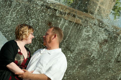 Happy Couple Posing with Fountain. Happy Caucasian couple embracing each other in front of a waterfall.  They are looking into each others eyes with love in Royalty Free Stock Photography