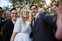 Happy couple posing with guests during wedding. In park stock photos