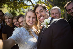 Happy couple posing with guests during wedding. In park royalty free stock image