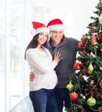 A happy couple posing near the Christmas tree. A happy couple (pregnant women and a man) posing near the Christmas tree. The image is taken on a light interior Royalty Free Stock Photo