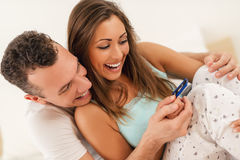 Happy Couple With Pregnancy Test. Beautiful young loving couple sitting on the bed with a smile on their face looking at pregnancy test stock image