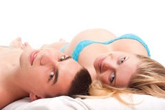 Happy couple - pregnant woman with her husband. Pregnant woman with her husband laying on white and smiling. Studio shoot on white Royalty Free Stock Photo
