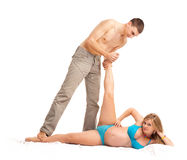 Happy couple - pregnant woman with her husband. Pregnant woman with her husband doing exercises. Studio shoot on white Royalty Free Stock Photography